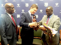 Mr Buah (right), presenting a gift to his Russian counterpart, Mr Alexander Novak.