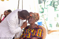An old woman getting her eye checked by a doctor