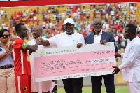 Kotoko skipper Amos Frimpong receiving the dummy cheque from Perry Okudzeto