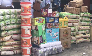 Items presented include bags of rice, soft drinks, medical supplies, washing powders