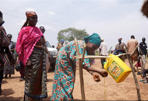 Women washing hands under tippy tap, men installing tippy tap