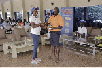 Solomon Allotey is all smiles as he receives the winner's trophy from Gifty Appiah of Latex Foam