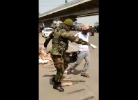 A shot of a soldier instructing a civilian to undertake frog jumps