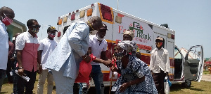 Emmanuel Armah Kofi Buah giving food items to some constituents