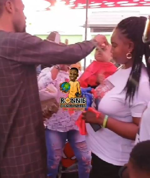 Rev Obofour spraying money on his one year old son