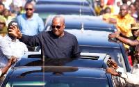 President John Mahama waves from car.     File photo.