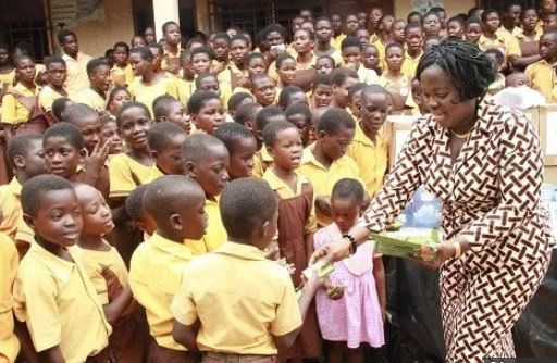 A representative from the foundation distributing chocolates to the school children