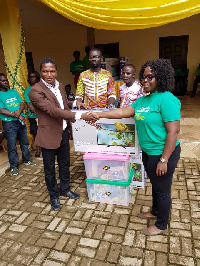 Mercy Quansah Ansah presenting the items to one of the teachers who assisted pupils to read