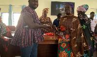Alhaji Habib Iddrisu (left)handing the money to one of the beneficiary women