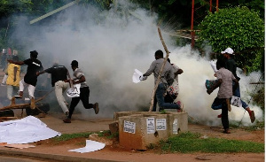 Protesters run from tear gas fired by police in Abuja