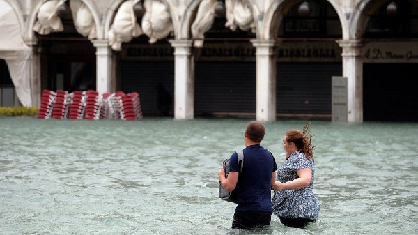 Some people donned thigh-high wellies or took off their shoes to wade through the water.