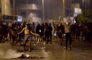 Protesters gesture as they block a street in the Sidi Hassine suburb on the outskirts of Tunis
