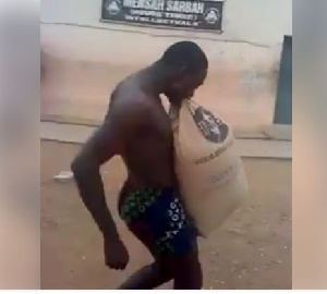 Man carrying a bag of cement with his teeth