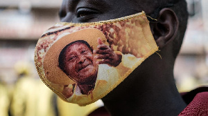 A supporter of the National Resistance Movement (NRM) wears a protective face mask