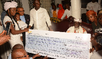 Mr. Ernest Nunoo presenting the dummy cheque to the Chief Imam as others look on