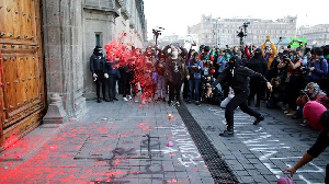 Demonstrators throwing paint at the door of the National Palace during the protest.