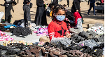 A girl wearing a protective mask amid the COVID-19 pandemic sells slippers in an open air market