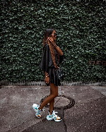 Lady rocking her chunky sneakers with a silk dress and side bag