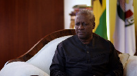 President John Mahama seated in his office