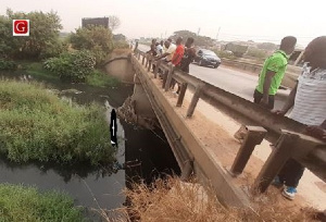 The dead man (arrowed) lying in the drain at Ashaiman