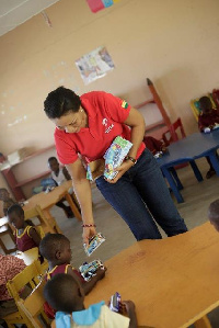 Hannah Agbozo, Legal & Corporate Affairs Director distributing  drinks to the kids
