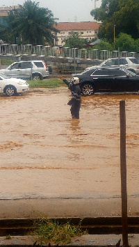 The policeman on duty directing vehicles in the flood
