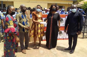 A photo of the principal of the school receiving the donation on behalf of the school