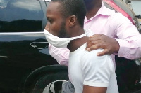 Ebenezer Osei  being whisked away by a cop