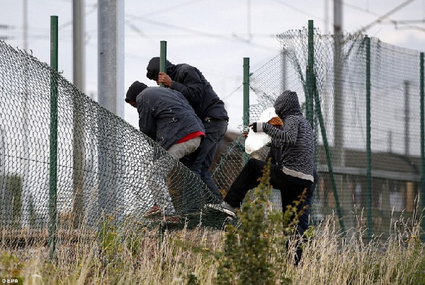 Migrants climb over a flimsy fence in Calais hoping to reach the UK