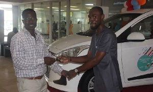 West Hills Centre Manager, Mr. Quarmson presents keys to the brother of the winner, Mr. Yawson.