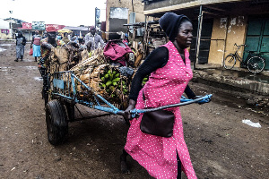 A woman pulls a cart of matooke in Busia Market