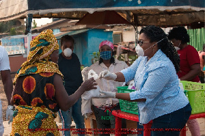 Naa Momo Lartey gifts a woman with some food stuff