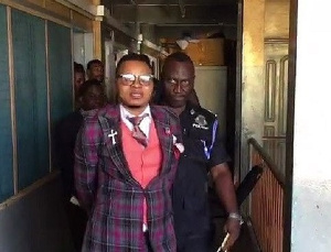 A photo of Obinim in police grips