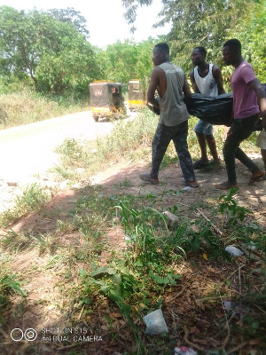 The remains of the suspect being carried by some residents