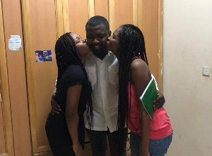 Actor John Dumelo sandwiched between two ladies