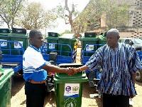 Mr John Sackey (left) handing over waste bins and motorized tricycles to Mr Joseph Amiyure
