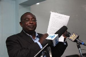 Mr Augustine Niber holding a copy of the report