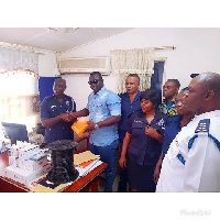 Nana Ofori Atta presenting the security items to the Kwabenya Police station