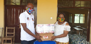 Madam Charity A.F. Dwommoh (DCE) handing the items to Mr. Mark Domah, Education Director.