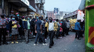 Commuters wait for a bus to return to home before a new 8pm-4am curfew in downtown Nairobi, Kenya