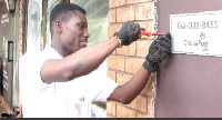 Jones Adzayoo tagging a digital address plate in front of Honeysuckle Pub and Restaurant building