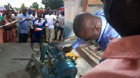Samuel Abu Jinapor cutting the sod and also inspecting the grinding mills