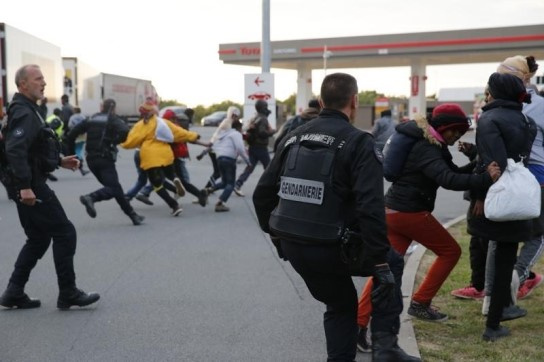 French gendarmes chase migrants as they attempt to access Calais Channel Tunnel