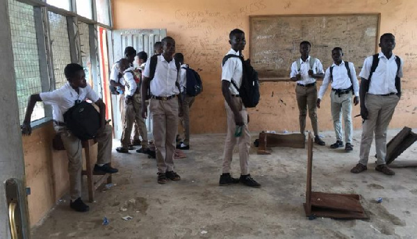 Some of the students leaning against the classroom walls