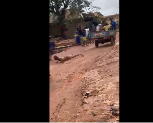 The suspected criminal tied to the tricycle and being dragged on the muddy road