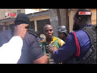 Gregory Afoko being escorted by Police personnel