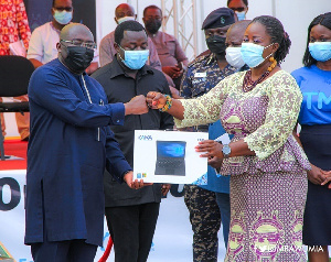 Vice President Dr. Mahamudu Bawumia presenting a laptop to a teacher