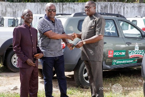 Former President Mahama (middle) donating the cars to the Chairman and general secretary of NDC