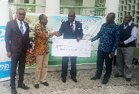 Executive Director of Unibank, Duke Mettle [Middle] presenting the cheque to Dr Bambangi