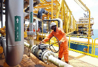 A Ghana Gas operations officer examining a pipeline